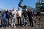 Projectleider Jan Blom (Haven Amsterdam), met  schep, en Frans Rodenburg, geflankeerd door werkmeesters en deelnemers van School2Work bij de officiële start van de reconstructie van de eendenkooi van Ruigoord.